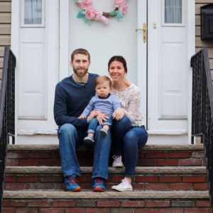 Family sits on porch of rental property