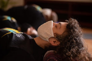 A person wearing a face mask with their head supported by a pillow